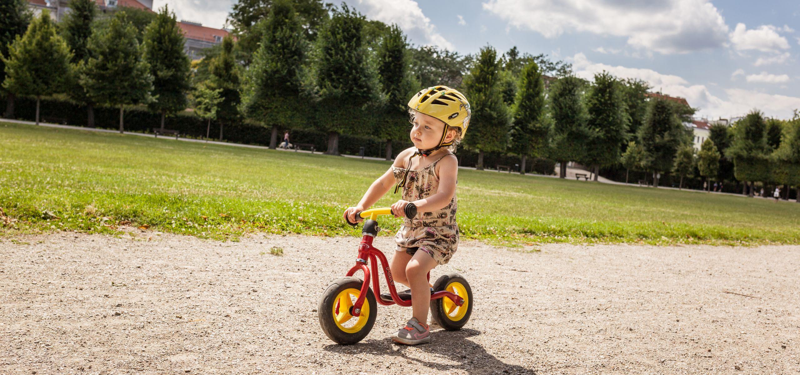 Kleines blondes Mädchen fährt mit einem Laufrad im Augarten.