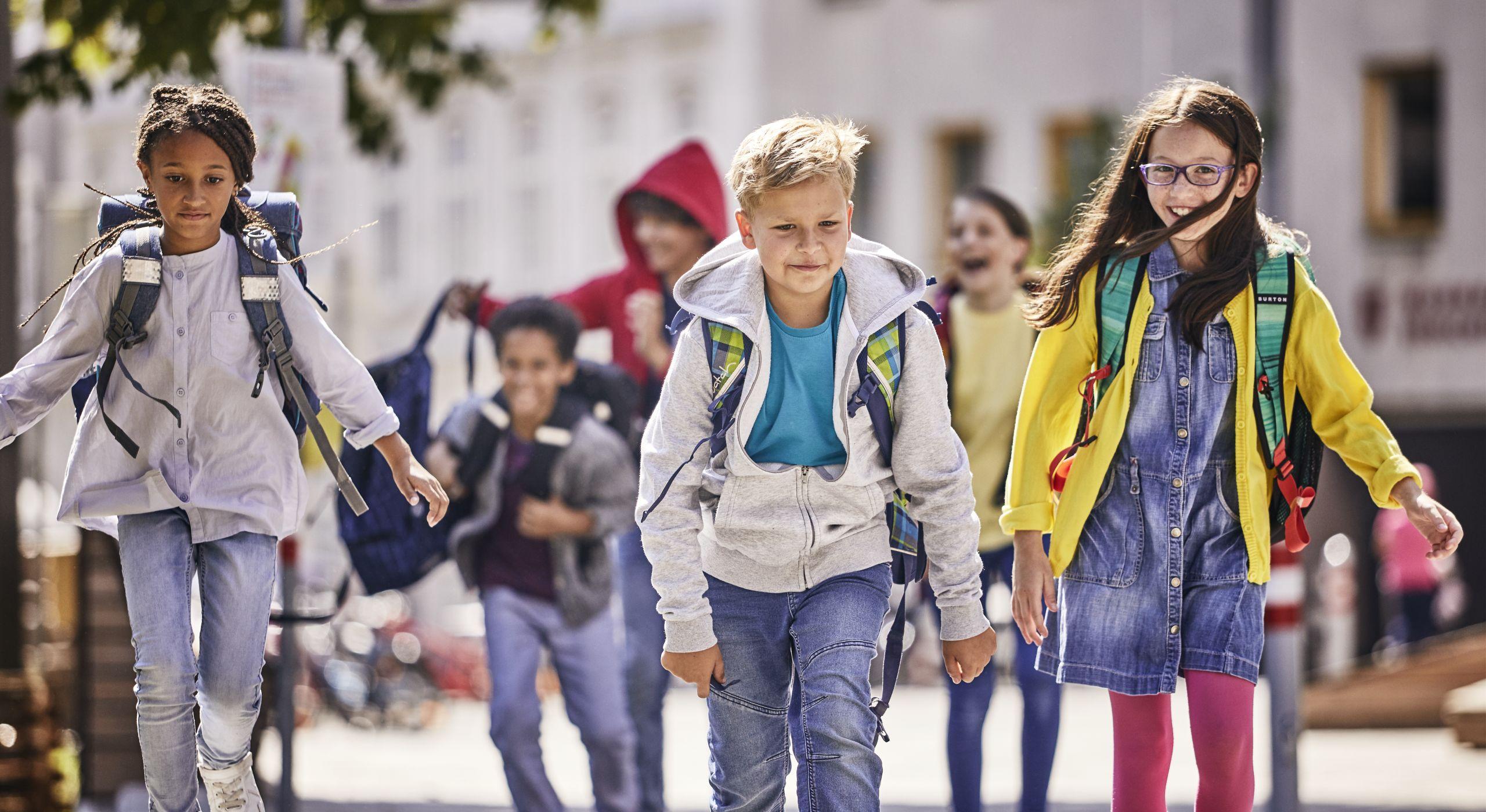 Ein Bub und zwei Mädchen auf dem Schulweg