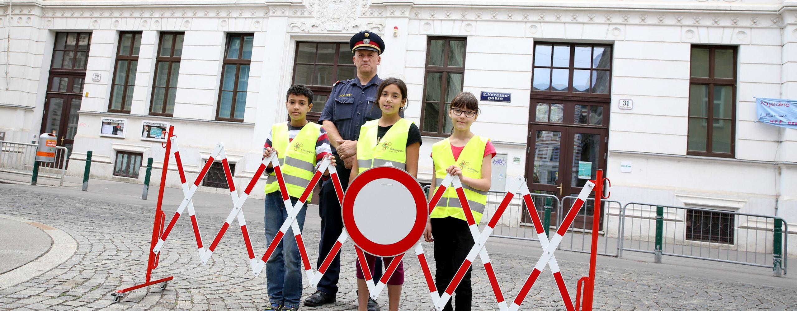Polizist und Schülerinnen und Schüler sichern die Schule während eines Fahrverbots mit Scherengitter.